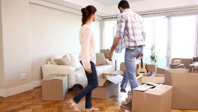 Attractive couple moving boxes into their living room. In their new home stock footage