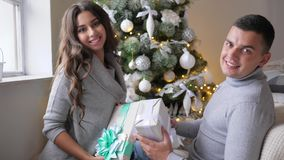 Attractive couple with New Year`s gifts looks in camera on background of decorated fir tree. Attractive couple with New Year`s gifts looks in camera on the stock video footage