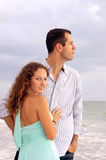 Attractive couple at ocean he is looking at sea sh. An attractive well dressed young couple  with their bodies facing each other, the man is looking out to the Stock Photography