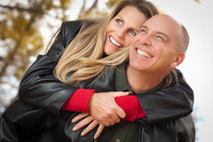 Attractive Couple in Park with Leather Jackets Royalty Free Stock Photography