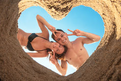 An attractive couple playing around on the beach. Young couple on the beach bottom up through heart of sand Stock Images