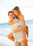 Attractive Couple Playing on the beach at Sunset Royalty Free Stock Photos