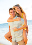 Attractive Couple Playing on the beach at Sunset Stock Photos