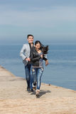 Attractive couple playing catch-up on concrete pier Royalty Free Stock Images