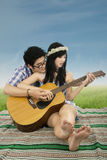 Attractive couple playing guitar at field Stock Images