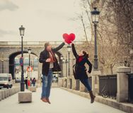 Attractive couple playing with a love heart pillow. Young attractive women throwing a love heart shaped pillow to her boyfriend Royalty Free Stock Photo