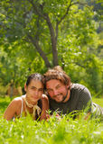 Attractive couple portrait. Young attractive couple smiling and lying on a grass Stock Images