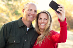 Attractive Couple Pose for a Self Portrait. Happy, Attractive Couple Pose for a Self Portrait Outdoors Royalty Free Stock Image