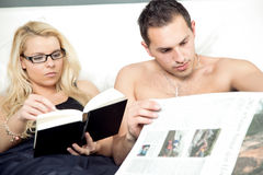 Attractive couple reading in bed together Royalty Free Stock Image
