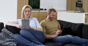 Attractive couple relax using tablets stock video