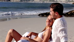 Attractive couple relaxing on the beach. And talking together stock video footage