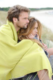 Attractive couple relaxing on the beach in warm clothing on a bright but cool day Stock Photos