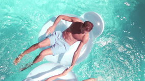 Attractive couple relaxing on lilos in pool. In slow motion stock video