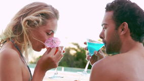Attractive couple relaxing by the pool. In slow motion stock footage