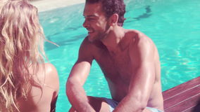 Attractive couple relaxing by the pool. In slow motion stock video