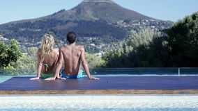 Attractive couple relaxing by the pool stock video footage