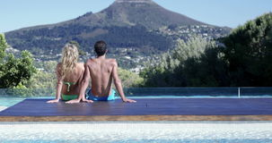 Attractive couple relaxing by the pool. On a sunny day stock video footage