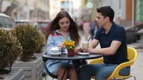 Attractive couple relaxing in sidewalk cafe stock video
