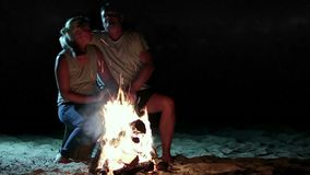 Attractive couple resting near bonfire at night stock footage