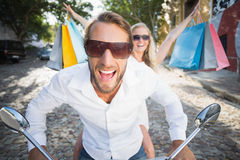 Attractive couple riding a scooter Stock Photo