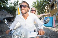 Attractive couple riding a scooter Royalty Free Stock Photos
