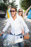 Attractive couple riding a scooter Royalty Free Stock Images