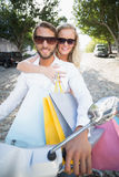 Attractive couple riding a scooter Stock Photos