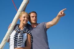 Attractive couple on sailing boat: man pointing with forefinger. Handsome male pointing with forefinger at something - couple on sailing boat stock photo