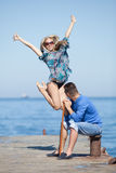 Attractive couple at the sea. Limp young men is observing a  hopping girl Royalty Free Stock Image