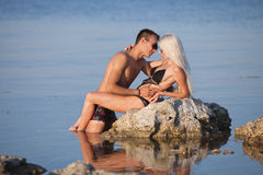 Attractive couple at the sea. Attractive couple flirting on wild rock at the sea Stock Images