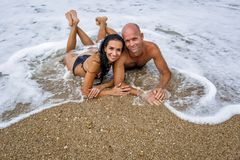 Attractive couple at the sea in summer overcast day. Man and women in swimwear lying on front on wet sand in sea foam. They cuddling shoulder to shoulder stock image