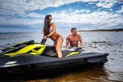 Attractive couple of a girl and shirtless muscular male have fun with a jet ski on a seacoast. An attractive couple of a girl and shirtless muscular male have Royalty Free Stock Photography