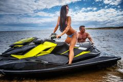 Attractive couple of a girl and shirtless muscular male have fun with a jet ski on a seacoast. An attractive couple of a girl and shirtless muscular male have Royalty Free Stock Photo