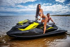 Attractive couple of a sexy girl and shirtless muscular male have fun with a jet ski on a seacoast. An attractive couple of a sexy girl and shirtless muscular Stock Photography