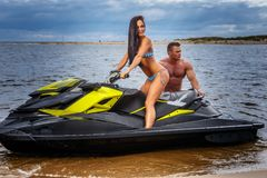 Attractive couple of a sexy girl and shirtless muscular male have fun with a jet ski on a seacoast. An attractive couple of a sexy girl and shirtless muscular Stock Image