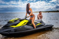 Attractive couple of a sexy girl and shirtless muscular male have fun with a jet ski on a seacoast. An attractive couple of a sexy girl and shirtless muscular Stock Images