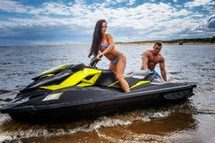 Attractive couple of a sexy girl and shirtless muscular male have fun with a jet ski on a seacoast. An attractive couple of a sexy girl and shirtless muscular Stock Photo