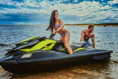 Attractive couple of a sexy girl and shirtless muscular male have fun with a jet ski on a seacoast. An attractive couple of a sexy girl and shirtless muscular Royalty Free Stock Images