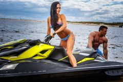 Attractive couple of a sexy girl and shirtless muscular male have fun with a jet ski on a seacoast. An attractive couple of a sexy girl and shirtless muscular Royalty Free Stock Photos