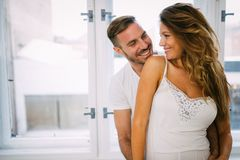 Attractive couple sharing intimate moments in bedroom. Attractive young couple sharing intimate moments in bedroom Royalty Free Stock Photography