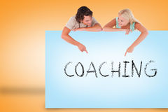 Attractive couple showing card with coaching Stock Photography