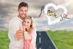 Attractive couple showing thumbs up to camera. Against road on grass Royalty Free Stock Image
