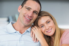 Attractive couple sitting on the couch smiling at camera Royalty Free Stock Photography