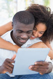Attractive couple sitting on couch together looking at tablet Stock Images