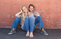 Attractive couple sitting on ground Royalty Free Stock Image