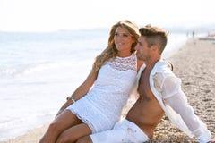 Attractive couple sitting on pebble beach. Stock Photos