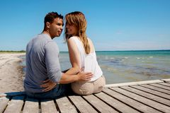 Attractive Couple Sitting on a Pier Royalty Free Stock Photography