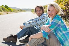 Attractive couple sitting on the road smiling at camera Stock Images