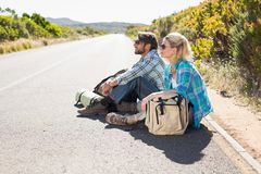 Attractive couple sitting on the road waiting for a lift Stock Images