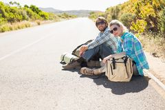 Attractive couple sitting on the road waiting for a lift Stock Photos
